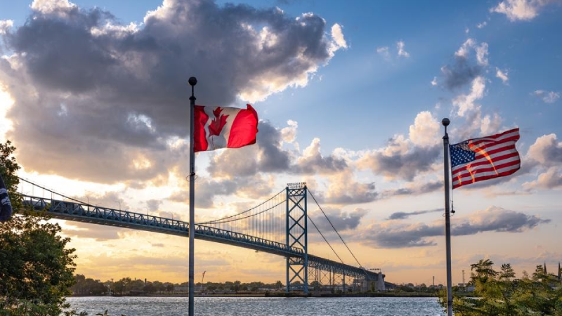 Canada and U.S. flags by land border bridge.